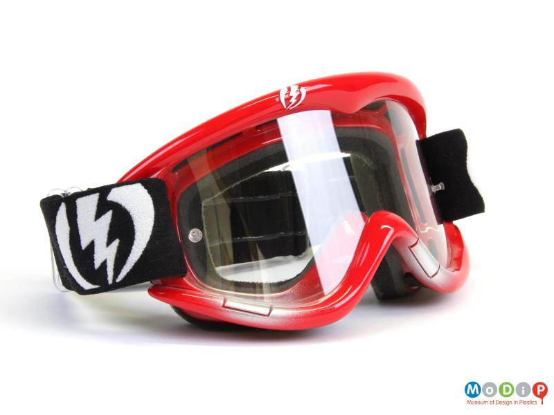 Side view of a pair of Electric goggles showing the clear lenses and red frames.