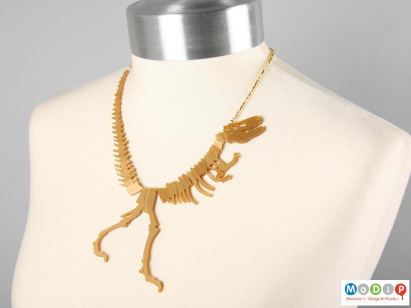 Front view of a Tatty Devine necklace showing the shape of the dinosaur on the neck of a mannequin.