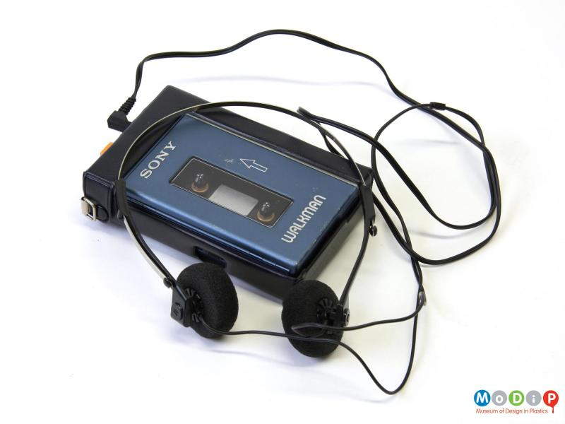 Top view of a Sony Walkman TPS-L2 personal cassette player showing the removable protective case, the closed cassette cover and the headphones.