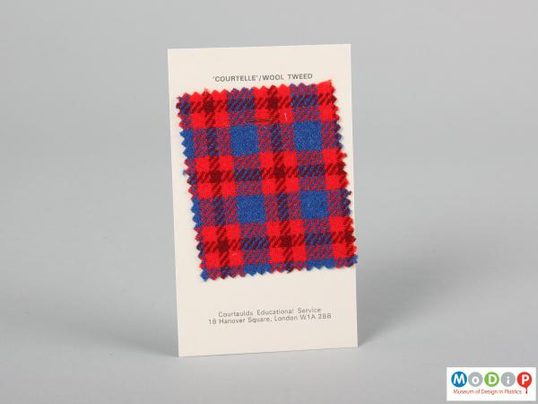 Front view of a fabric sample card showing the material stapled to the card.