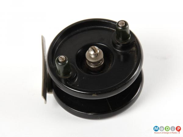 Side view of a fishing reel showing the circular shape.