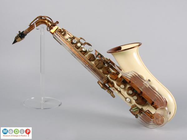 Side view of a saxophone showing the cream coloured and clear acrylic parts.