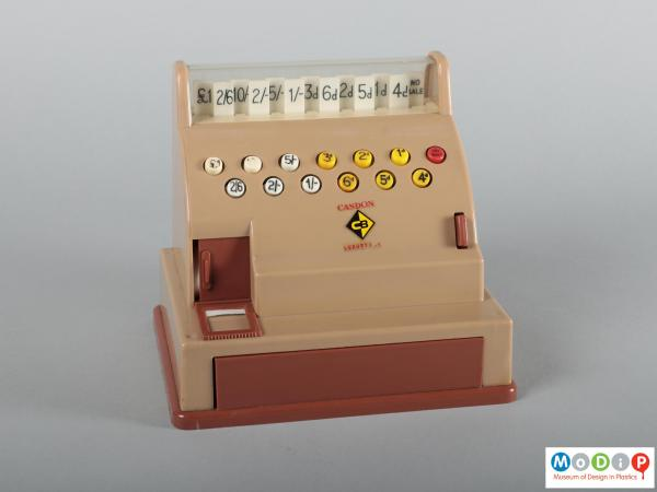 Front view of a toy till showing buttons and tabs.
